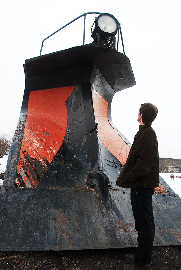 A person looking up at a huge snow-plow train car.