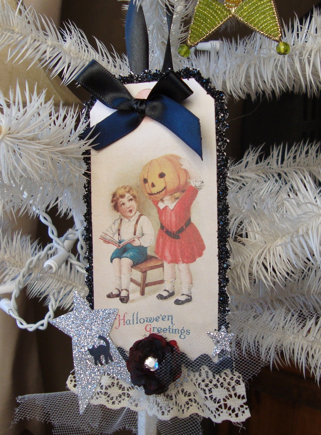 Vintage style black glittered Halloween altered tag ornament with little boy and girl