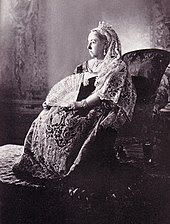 Seated Victoria in embroidered and lace dress