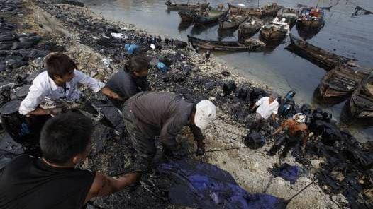 PRECARIEDAD. Con sus botes teñidos de negro, trabajadores levantan bidones con el crudo extraído. (AP)