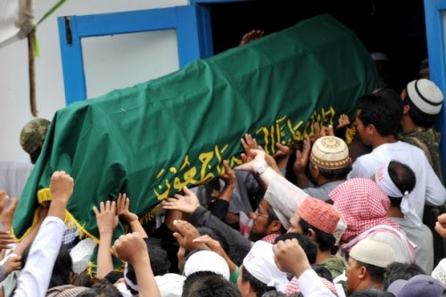 """Supporters carry a coffin containing either Mukhlas or Amrozi (unclear) as they arrive at Al Islam boarding school in Tenggulun on November 9, 2008.  Grief and religious fervour boiled over into calls for revenge here as two brothers executed for their role in the 2002 Bali attacks were buried amid tight security.   A crowd of about 500 supporters briefly clashed with police near the family home of 47-year-old Amrozi -- dubbed the """"smiling assassin"""" for his disturbing grin -- and Mukhlas, 48, as their bodies arrived in their east Java village. AFP PHOTO/ADEK BERRY (Photo credit should read ADEK BERRY/AFP/Getty Images)"""