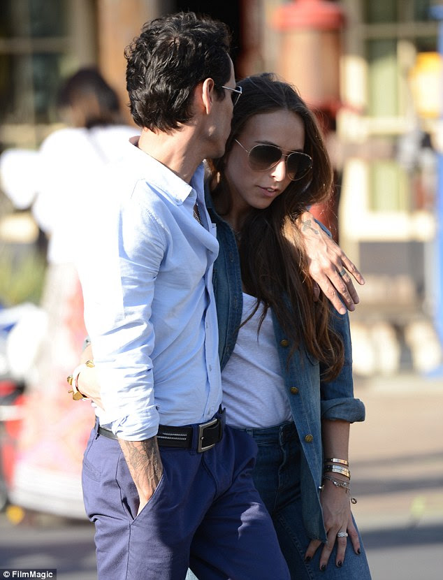 Close: The singer plants a kiss on his young girlfriend's head as they walk in the sunshine