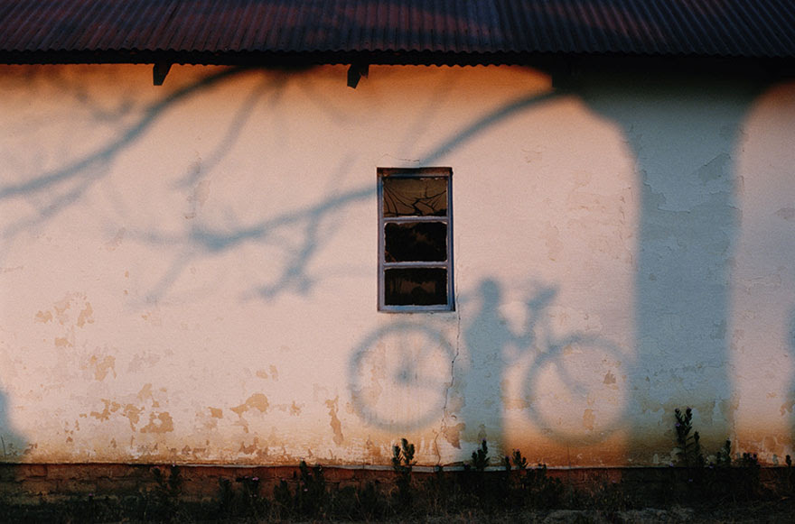 A Shadow Of A Man Holding A Bicycle Is Cast On A Wall Near The Zambezi River, 1996