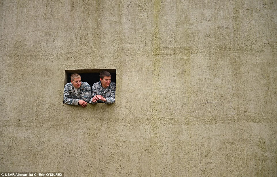 England: Airmen from the 48th Mission Support Group watch a training exercise from a building constructed as a mock village during a force-on-force exercise at Stanford Training Area in England. More than 130 48th MSG Airmen participated in the training exercises