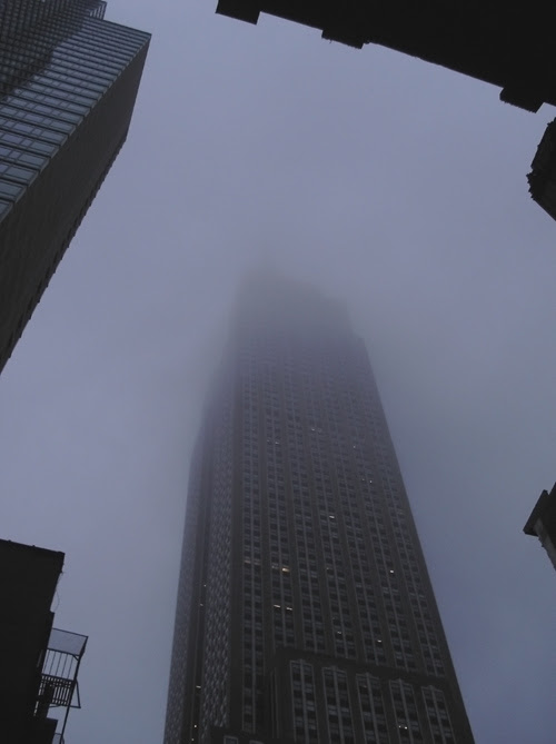 the top of the Empire State Building disappears into the clouds, NYC