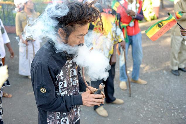 Homem fuma maconha em frente a museu de Bob Marley em Kingston, a capital jamaicana