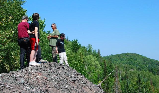 People on the edge of a huge rockpile.