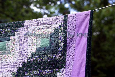 a log cabin pattern quilt on the clothesline