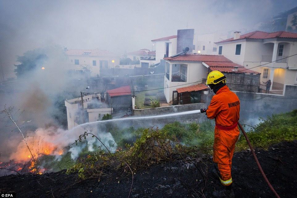 Um bombeiro Português mangueiras para baixo chamas em uma área residencial da cidade de Funchal, na Madeira.  Três pessoas são relatados para ter sido morto