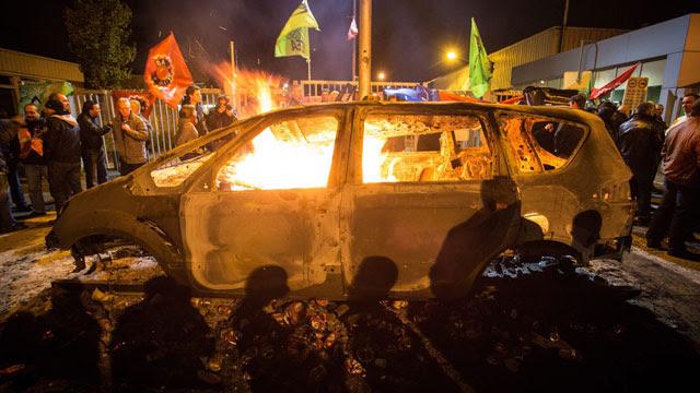 Un auto Ford arde en llamas durante la protesta del jueves en la fábrica de Genk.
