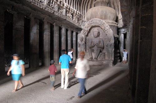 Ein Buddhaaltar unter einem Tonnengewölbe, mit zwei Säulenreihen, die die Halle in Mittelschiff und Seitenschiffe teilen. Durch Besucher sind die Grössenverhältnisse zu sehen.