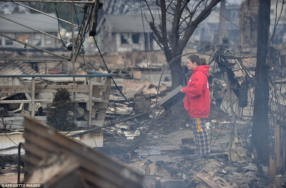 Lost in the fire: A woman stands among the still-smouldering remains of homes which burned down in the Breezy Point area of Queens in New York