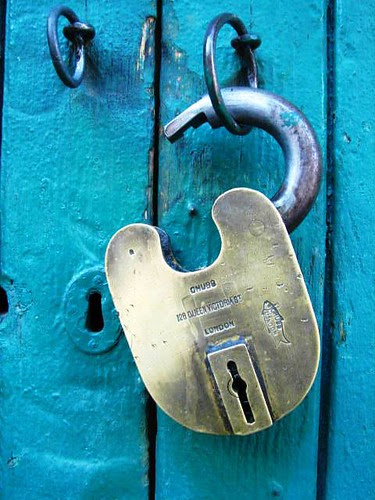 Brass padlock on green door