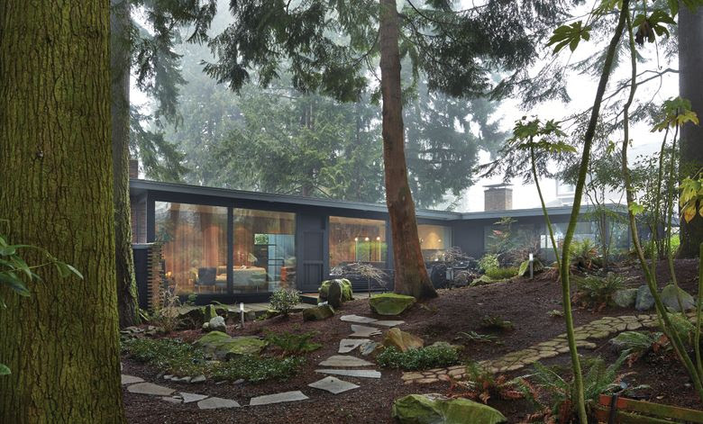 The L-shaped single-story house with a shed roof and concrete-block foundation is sited for privacy. Large window walls face the forested and newly groomed backyard. (Benjamin Benschneider)