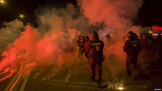 Police walk between flares thrown by right-wing protesters who are against bringing asylum seekers to an accommodation facility in Heidenau, Germany (August 22, 2015)