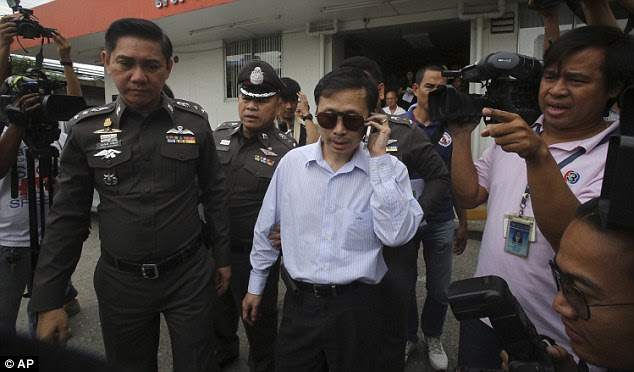 Doctor Sompob Sansiri, 51, is lead away by police after Miss Williams died at his clinic