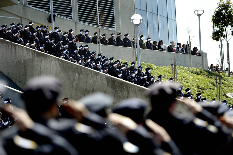 Thousands of law enforcement officers from several cities salute the four slain Oakland Police officers as they leave the Oracle Arena in Oakland, Calif.,  where they held the funeral services on Friday, March 27, 2009. Thousands of people and law enforcement officers from all over the nation and Canada paid tribute to Sgt.'s Mark Dunakin, Erv Romans, Dan Sakai and officer John Hege.  (Ray Chavez/Bay Area News Group Archives)
