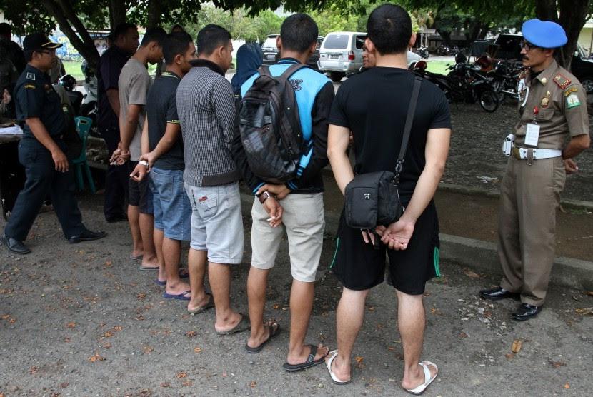 Petugas Satpol PP dan Wilayathul Hisbah (WH) memberikan pengarahan kepada warga yang terjaring razia penegakkan Syariat Islam kerena memakai celana pendek di Banda Aceh. (Ilustrasi)