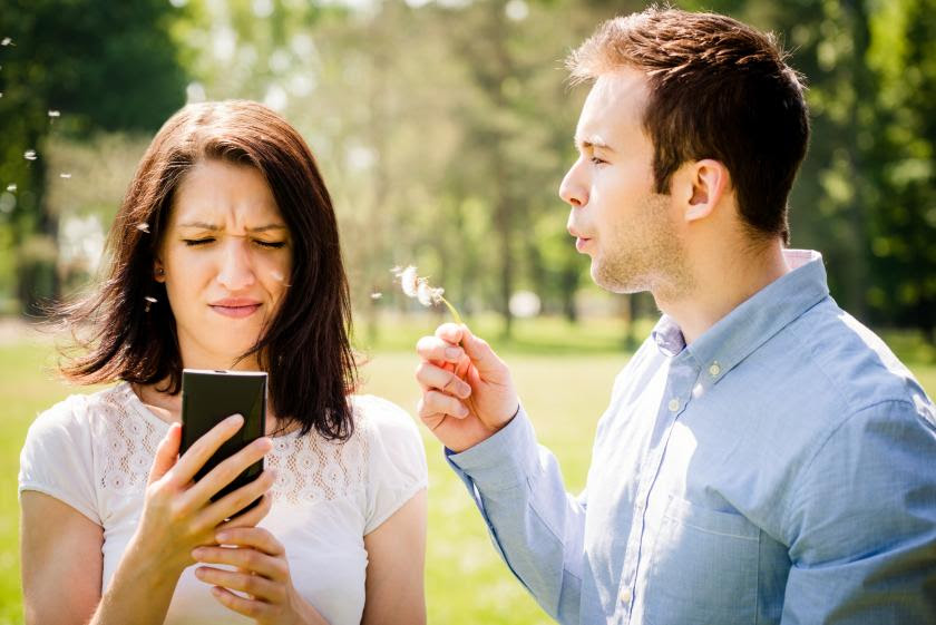 Young man blowing dandelion to face of angry woman holding mobile phone