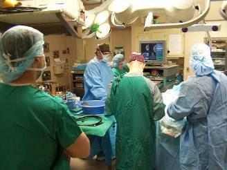 Foto de un quirófano con médicos operando a una paciente