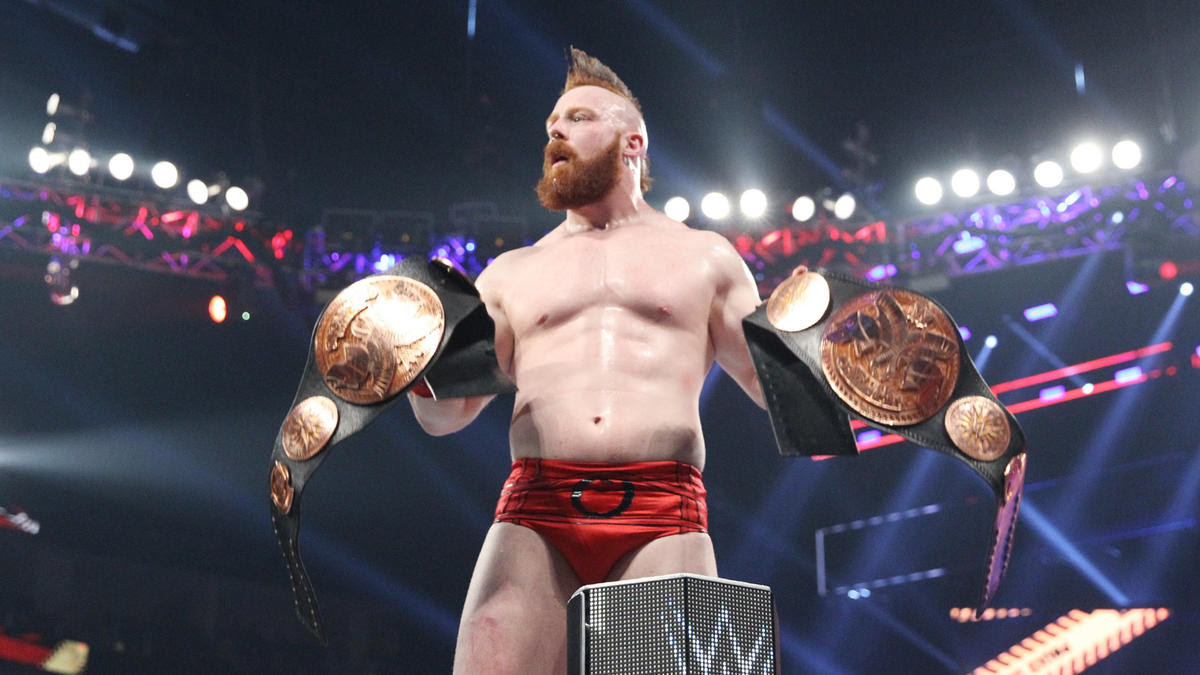 After snatching the titles from the defeated champions, Sheamus celebrates the victory with both prizes.