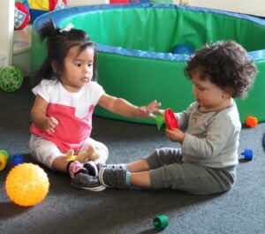 Zoe Calderón and Gerardo Herrera share toys at Pajaro Valley Unified's daycare center in Watsonville.