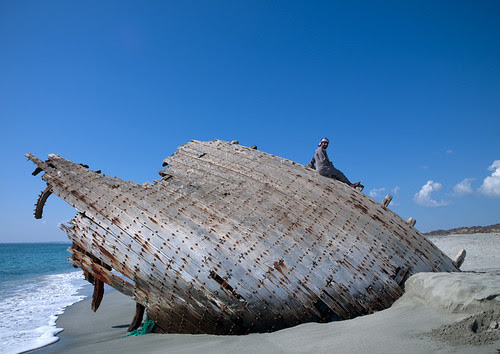 Man on a dhow wreck on the beach, Masirah Island, Oman by Eric Lafforgue