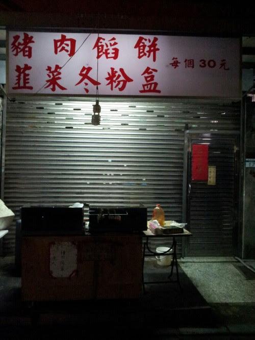 Taipei: a Back Alley 台北:豬肉饀餅 韮菜冬粉盒 一個三十元 午後七時過ぎの裏町、道幅四メートル足らずの裏通り。煌煌と店先を照らすランプが吊るされている。しかし店はすでにシャッターが下りている。道路にわずかながらはみだした鉄板焼のレンジが組み込まれた屋台がきれいに片付けられておいてあった。脇には調理台と棚も。盗人なぞ気にせず、このまま夜を越すのだろうか。看板には… 豬肉饀餅 韮菜冬粉盒 一個三十元 豚肉饅頭、表面をこんがりと焼いた饅頭。きっと肉汁が売り物だろう。もう一品は韮を細かく切り刻んで冬粉に混ぜ込み焼き上げるクレープ。どちらも三十元、日本円約百円。書いてある意味はそうだが、実物を見ていない。百円の価値ある食い物かどうか、昼間訪れてみることにした。 焼肉まんは十分大きく、韮のクレープの大きさは一尺はある。ソースをかけ、くるくると巻いて客に渡している。肉まんは旨そうだったが、肉汁を思うと私の腹は受け付けない。見るだけで退散してきた。