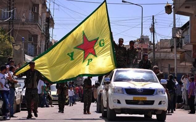 Des combattants kurdes des Unités de protection du peuple (YPG) agitent le drapeau de leur mouvement lors d'un défilé à Qamichli en février 2015. AFP