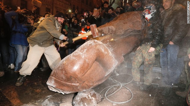 A Ukrainian protester slams a toppled monument of Vladimir Lenin in Kiev, Ukraine, on Sunday, December 8. Ukrainians occupied the square to denounce President Viktor Yanukovich's decision to turn away from Europe and align this ex-Soviet republic with Russia, as protests continued for a third week.