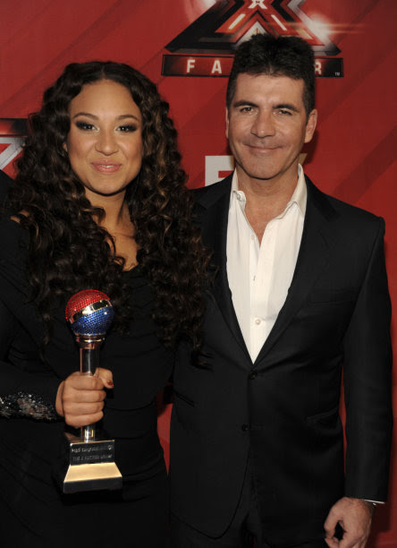 Singer Melanie Amaro, left, and television personality Simon Cowell pose together on the red carpet at The X Factor Finale show in Los Angeles on Thursday, Dec. 22, 2011. Amaro was chosen as the winner for the first season of the show. She will be awarded with a $5 million record deal and a Pepsi ad campaign.(AP Photo/Dan Steinberg)