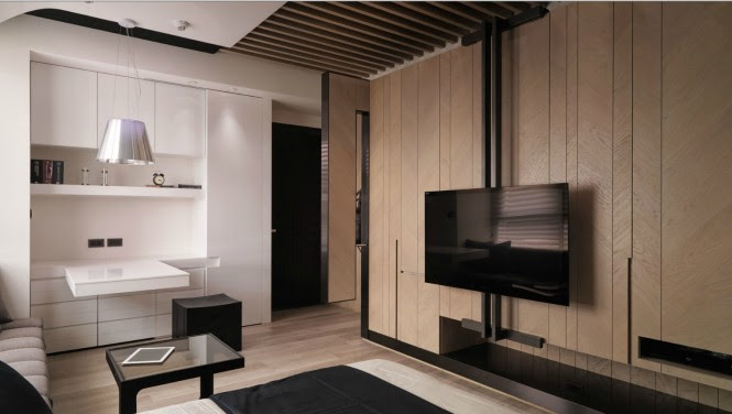 Opposite a muted gray sofa, an entertainment wall holds a flat screen TV in front of sleek wood paneling; storage cubbies for other paraphernalia such as DVD players, games consoles and accessories are built in.