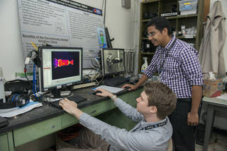 NASA engineers monitor temperature data on the left computer screen as a thruster fueled with the green propellantis fired.