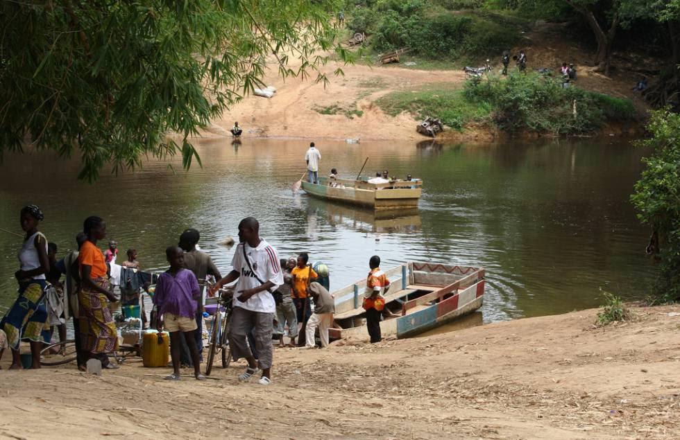 Varios viajeros cruzan un río en Liberia, uno de los países más pobres de África subsahariana.