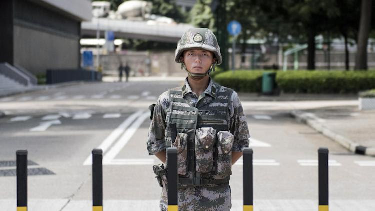 A Chinese People's Liberation Army (PLA) soldier stands guard at the entrance to the PLA's Hong Kong Garrison headquarters in Hong Kong on August 29, 2014