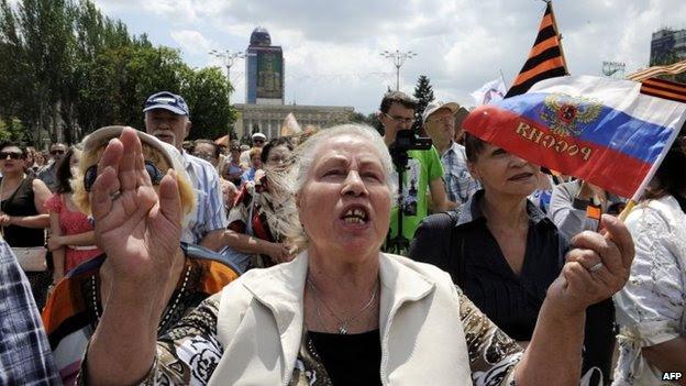 """Uma mulher ondas uma bandeira russa de militantes pró-Rússia fazer o juramento militar de fidelidade aos Republik de Donetsk """"s chamados Pessoas"""