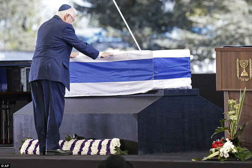 Colocando as mãos: presidente de Israel, Reuven Rivlin paga seus respeitos para o caixão coberto pela bandeira de Shimon Peres