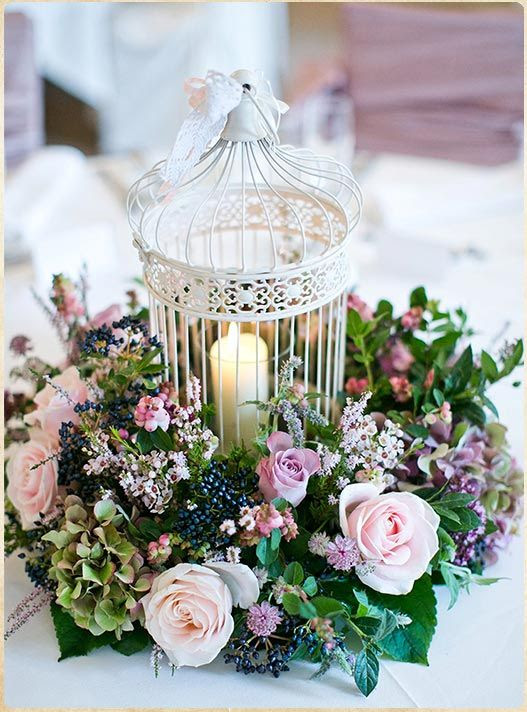 ein Käfig als eine Kerze-Halter und umgeben von üppigen Flieder blüht und grün