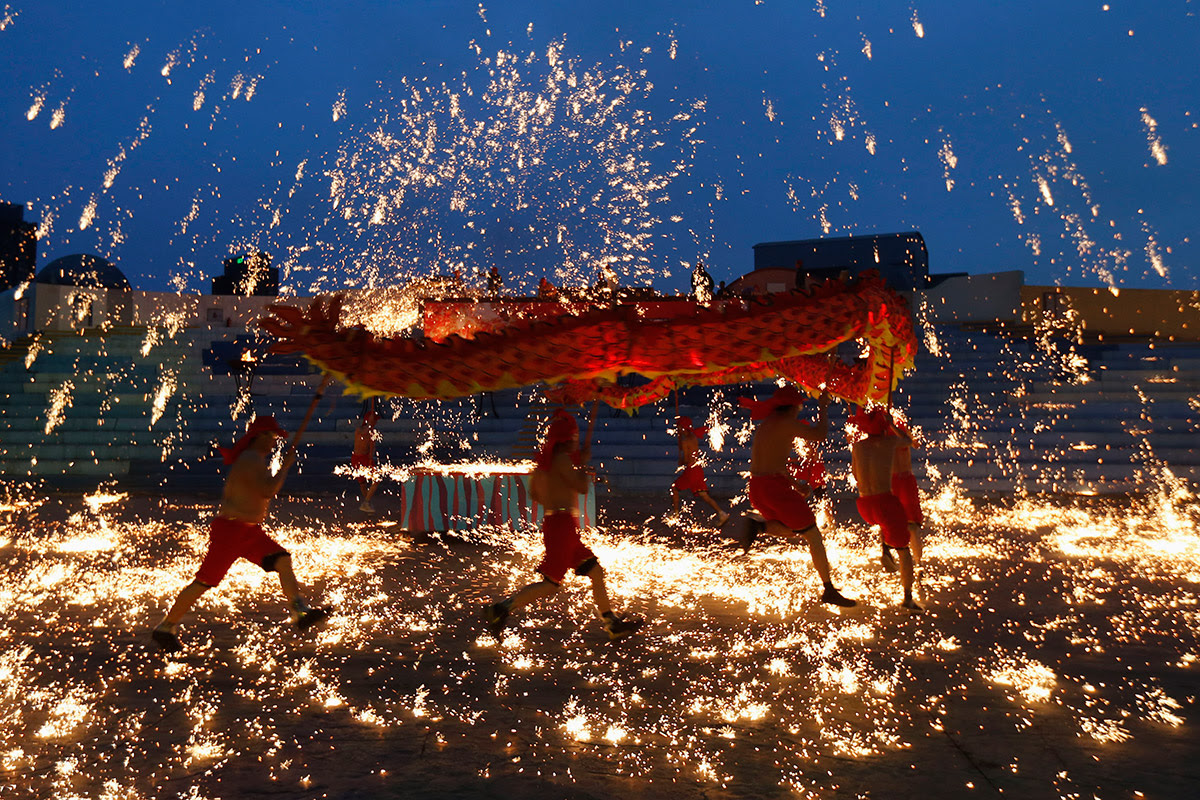 Dancers perform a fire dragon dance in a shower of molten iron in Beijing. Fireworks are let off to draw the attention of the God of Wealth, thus ensuring good fortune