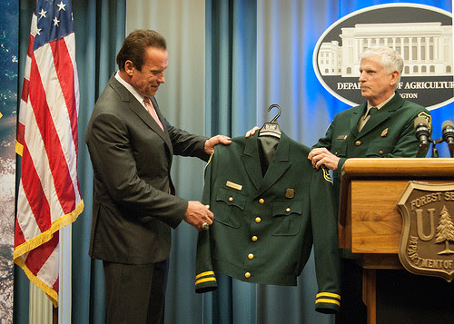 Chief Tom Tidwell presents former Governor Arnold Schwarzenegger with a Forest Service jacket.  Schwarzenegger was named an honorary forest ranger during a ceremony today at the USDA Whitten Building. (Photo by Bob Nichols, USDA)