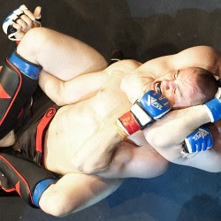 Corey Hinkley of CMBJJ-NEU, and from Lewiston, top, taps out under a choke hold from Dom Cofone of Balanced Ground during Saturday night's NEF XIV at the Androscoggin Bank Colisee in Lewiston.