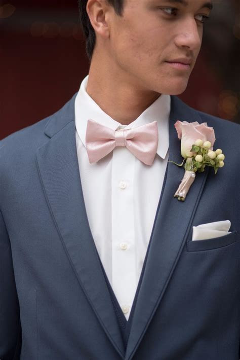 Blush pink bow tie and boutonniere with a slate blue suit