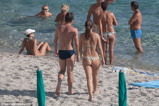 The former Italy boss and his wife Elisabetta Muscarello make their way towards the sea