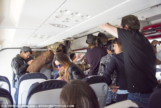 Blending in: The Hollywood stars and their large brood went seemingly unnoticed on the flight