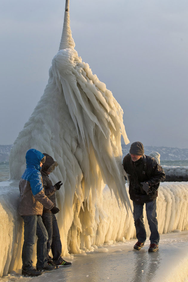 In this photo  Tuesday, Feb. 7, 2012 photo people stand next to a natural ice sculpture that was formed after the wind blew waves over the boardwalk of  Lake Geneva at the Port of Choiseul in Versoix