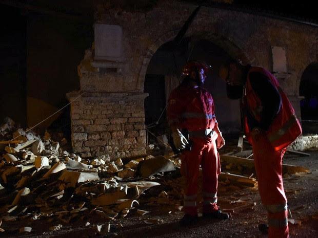 Bombeiros e funcionários de emergência são vistos próximos a escombros na vila de Visso, na Itália, após terremoto atingir o local na quarta (26) (Foto: Matteo Crocchioni/ANSA via AP)