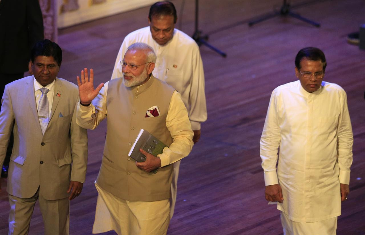 Indian Prime Minister Narendra Modi, center, waves as he leaves after the UN celebration ceremony of Vesak with Sri Lankan President Maithripala Sirisena, right, in Colombo, Sri Lanka, Friday, May 12, 2017. During his two-day visit Modi participated in the United Nations celebration of Vesak or the day of birth, enlightenment and death of the Buddha. He also inaugurated a modern hospital for the benefit of tea plantation workers , ancestors of Indian laborers brought by the British from the 18th century.
