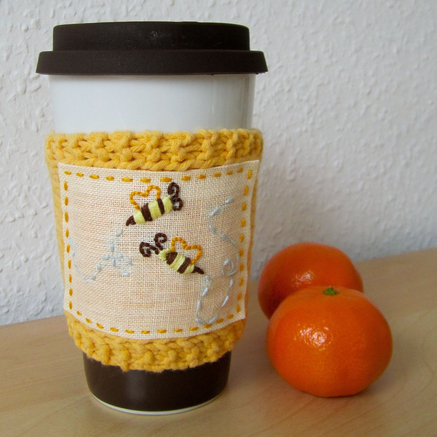 Reusable knitted coffee sleeve with embroidered honeybees.