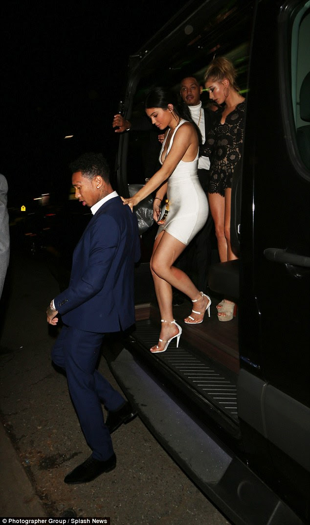 Altogether now: Kylie leaned on her man's sturdy form as she tottered out of the van, closely followed by her best pal