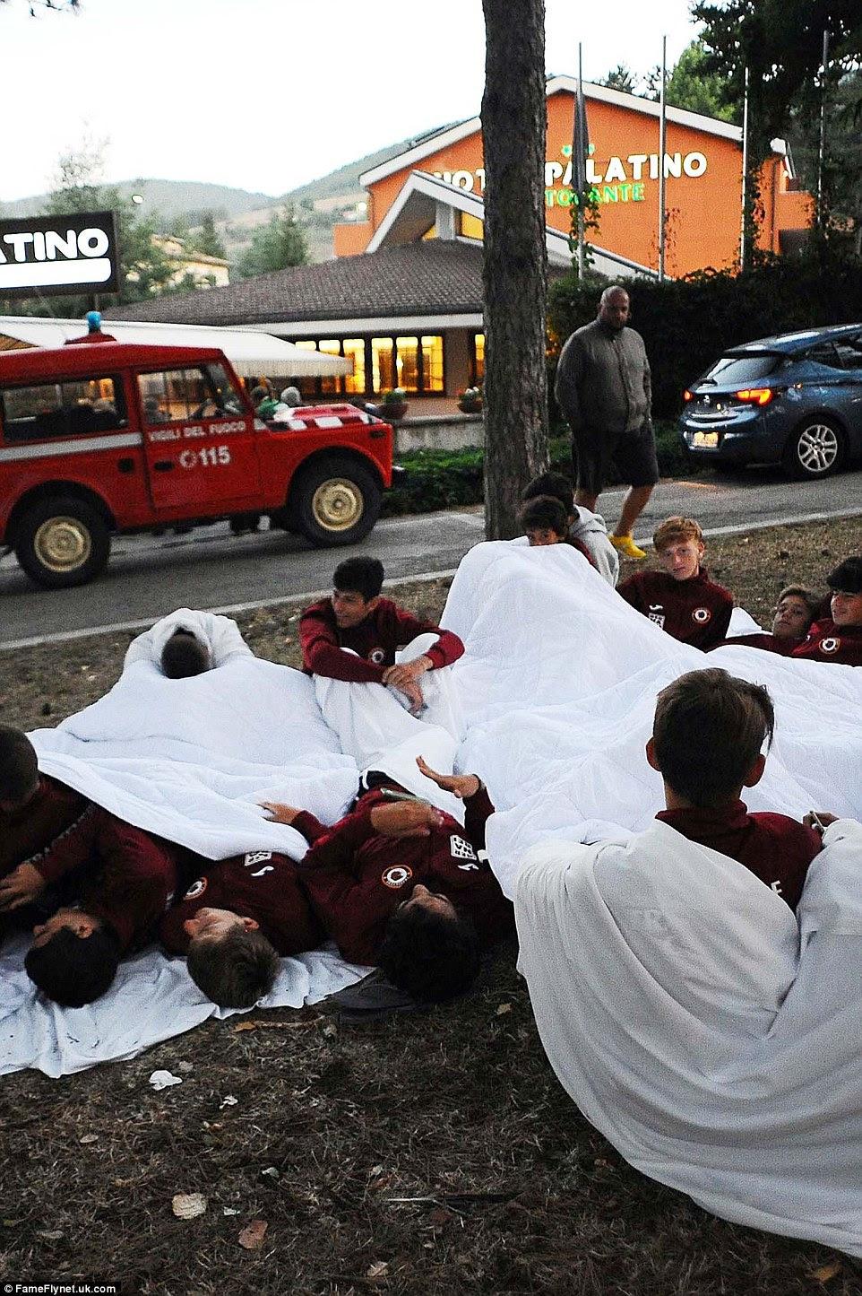 Juntos: A equipe de esportes repousa sobre o solo debaixo de cobertores brancos após a cidade de Amatrice foi atingido